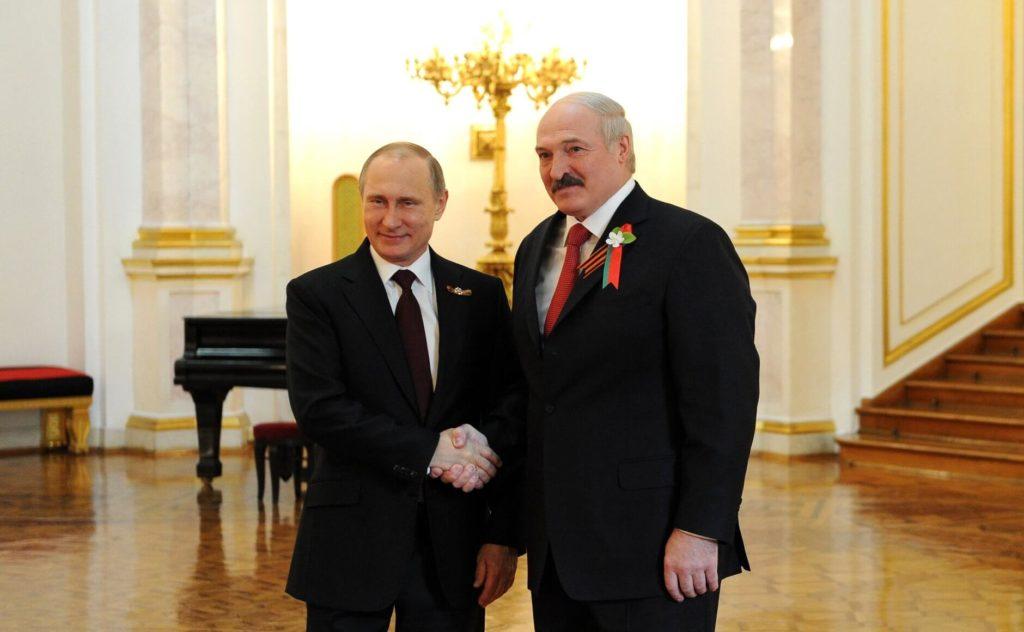 На фото В. Путин жмет руку А. Лукашенко.