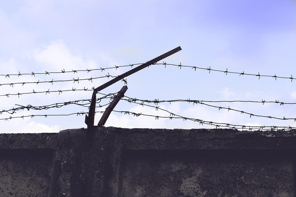 На фото изображена стена с колючей проволокой.