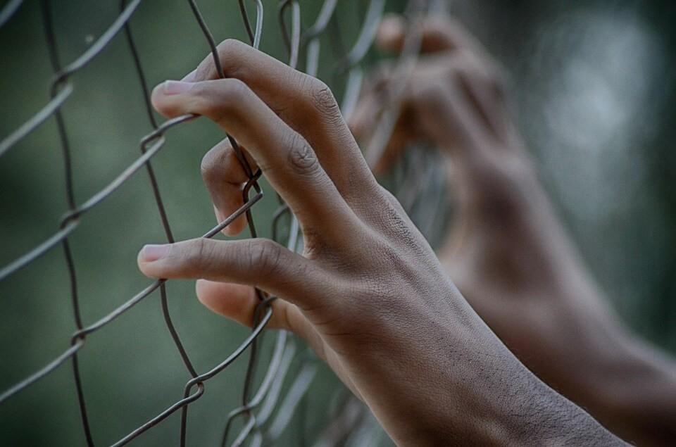 На фото человек держится руками за решетку.