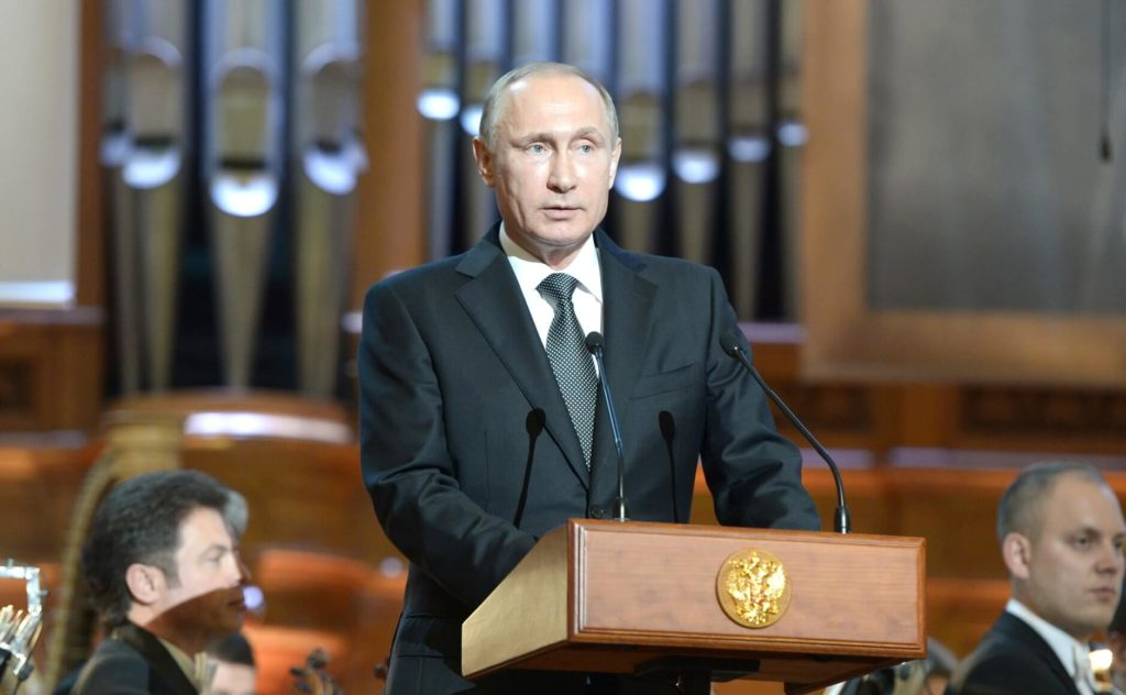 На фото изображен Владимир Путин за трибуной.