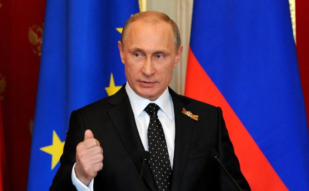 На фото изображен Владимир Путин на фоне флага РФ и ЕС.