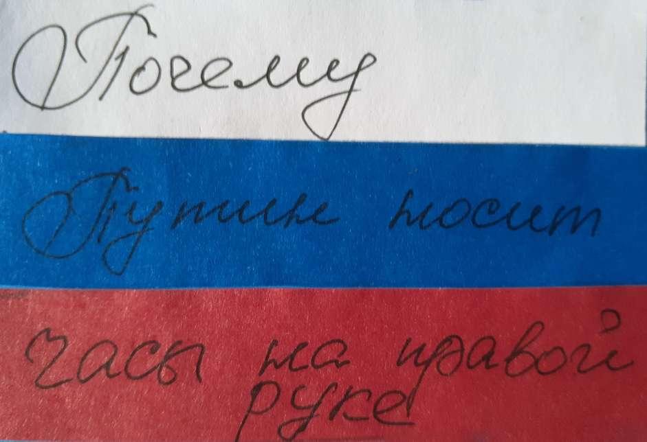 """На фото изображена надпись """"Почему Путин носит часы на правой руке""""."""