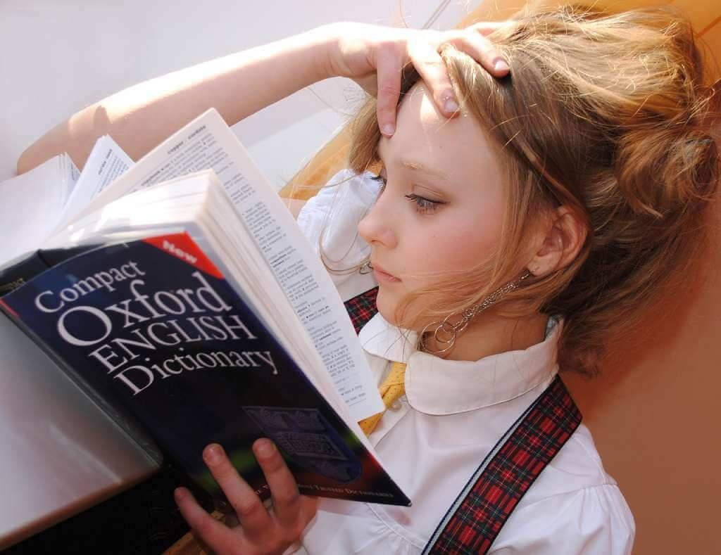 На фото девочка с книгой в руке.