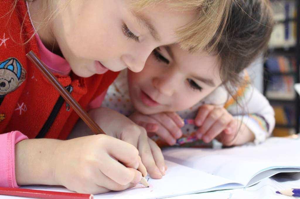 На фото дети пишут в тетради.